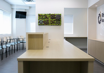 White glossy desk at reception area with live plant art